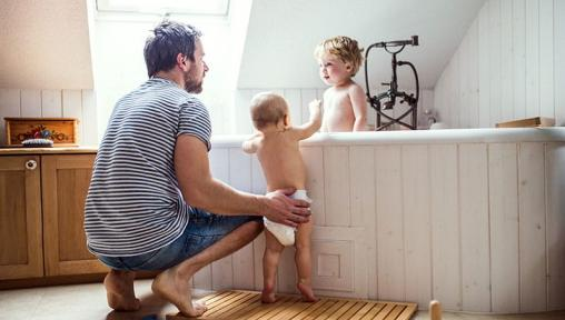 Father with toddlers in bath